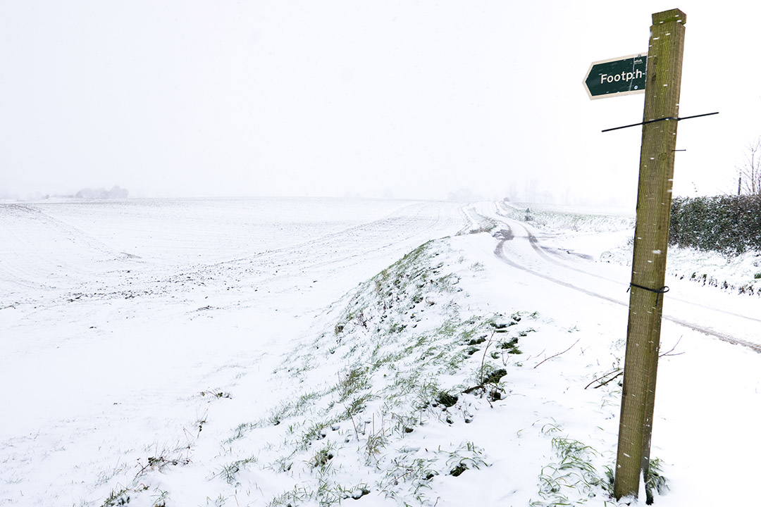 Snow covered fields with footpath sign