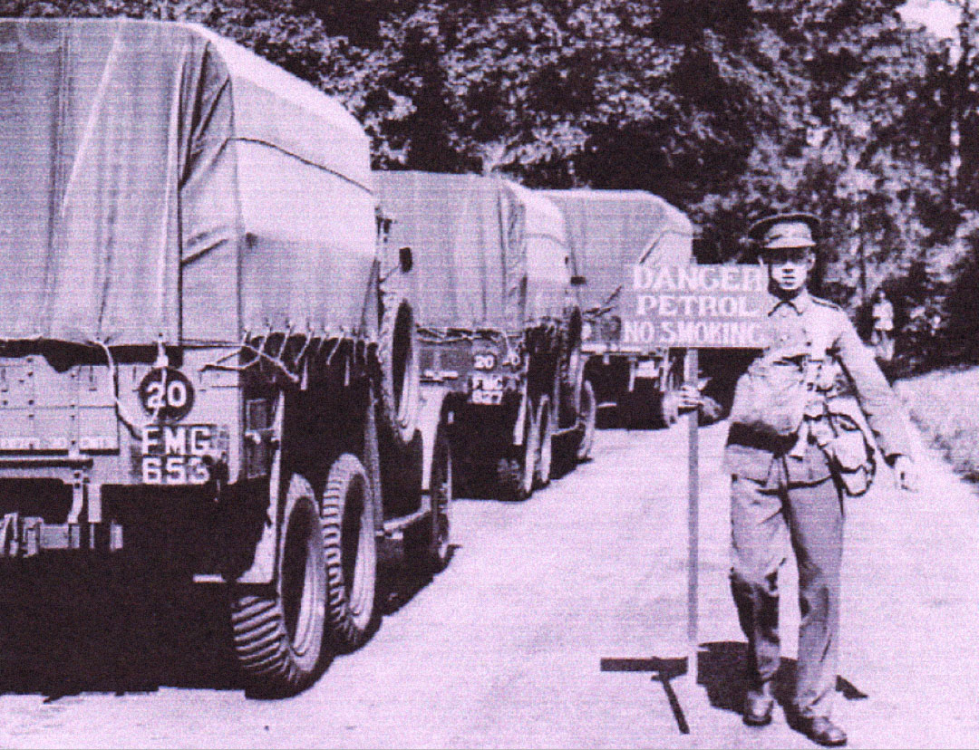 Old WW2 photo soldier with sign by convoy of trucks Coddenham