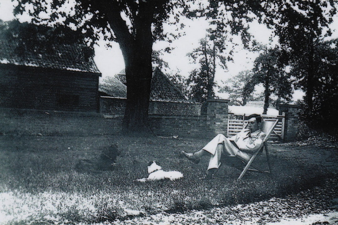 Old black and white photo man in deck chair in garden 1940