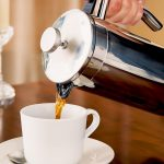 Pouring a cafetiere of coffee into a white cup